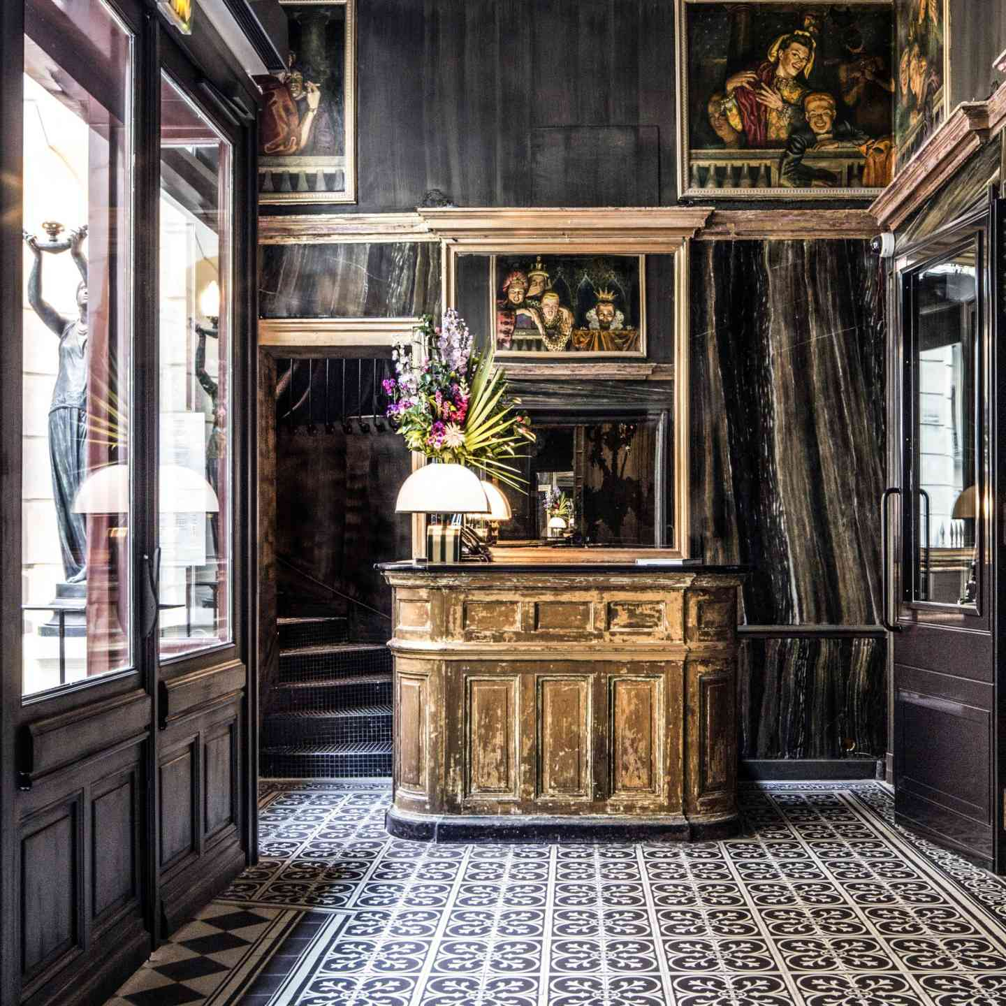 Boutique hotel lobby with vintage furniture and decor and a tile floor