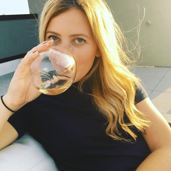 Aviel Kanter drinking white wine from stemless glass