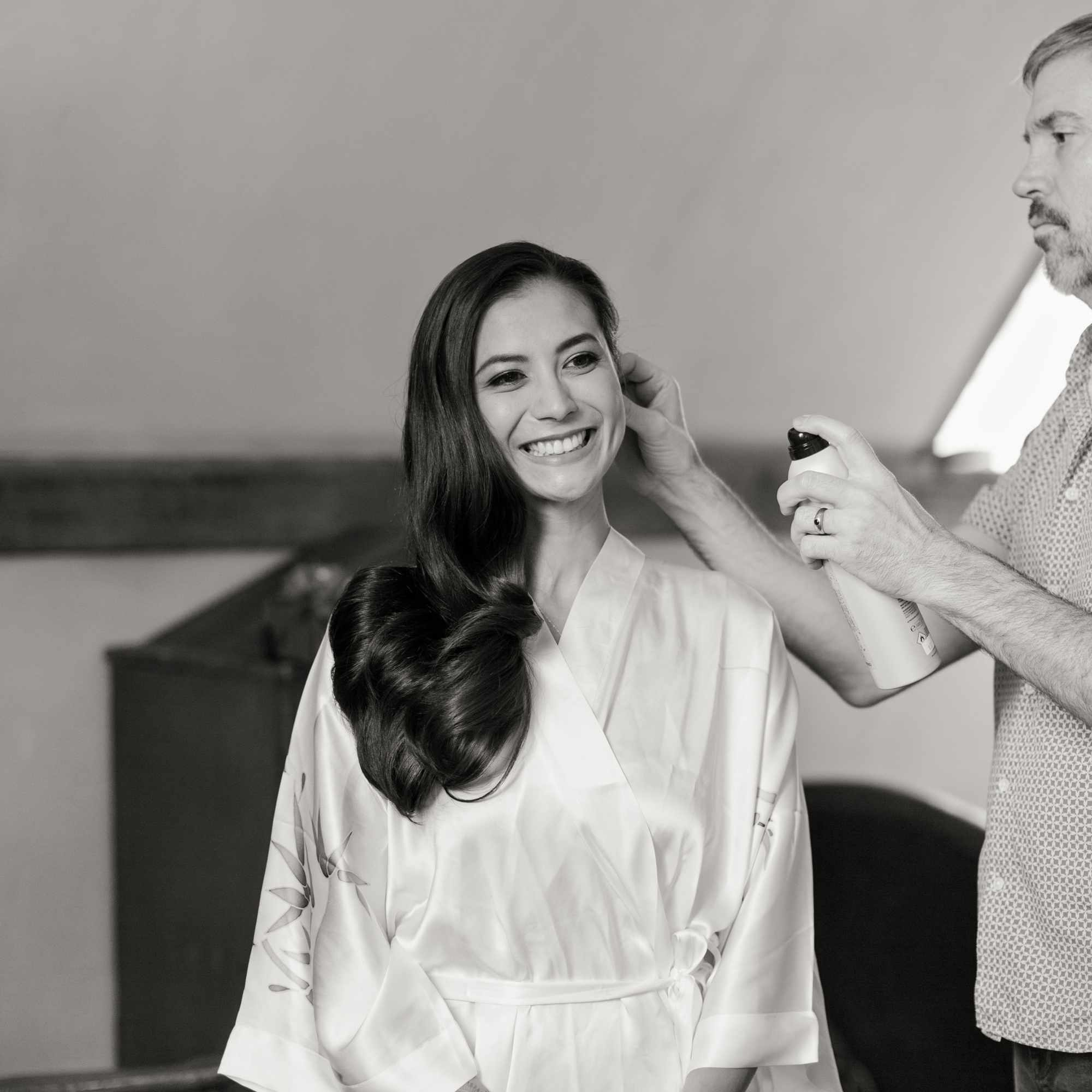 Hair stylist putting hair spray in brides shiny blowout