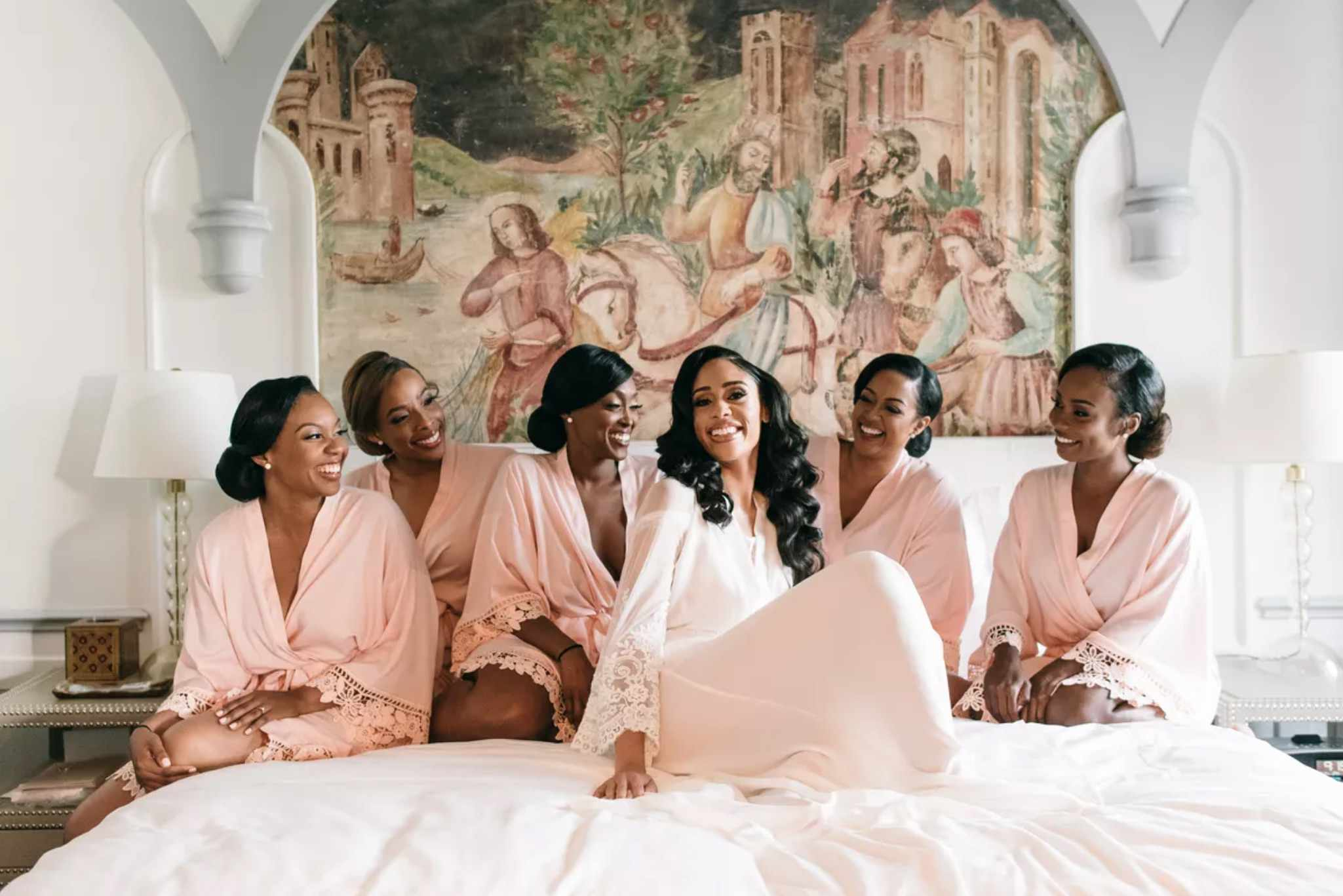 Bride and bridesmaids on bed