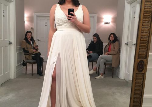 Woman trying on wedding gown and taking selfie.