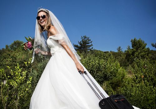 Bride in wedding gown pulling suitcase
