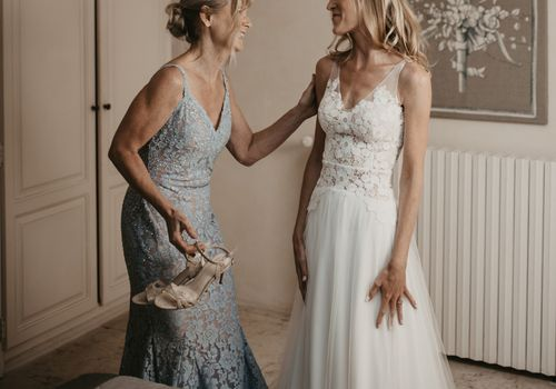Mother of the bride and bride smiling while getting ready in bridal suite