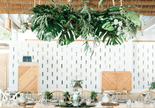 """Hanging greenery installation at a wedding with """"EAT DRINK DANCE"""" neon sign above it"""