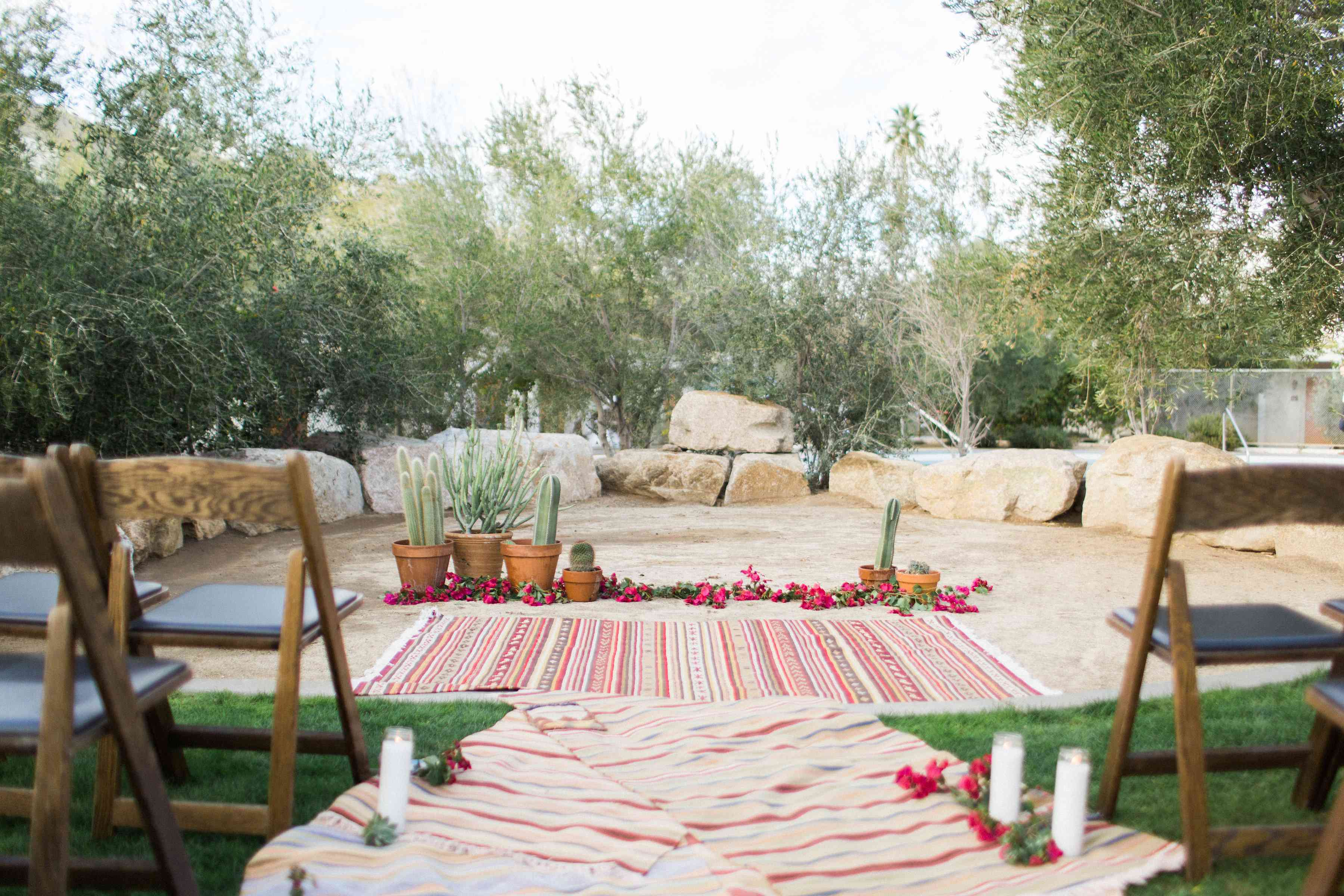 Wedding ceremony with rugs down the aisle and a rug with flowers and cacti at the end