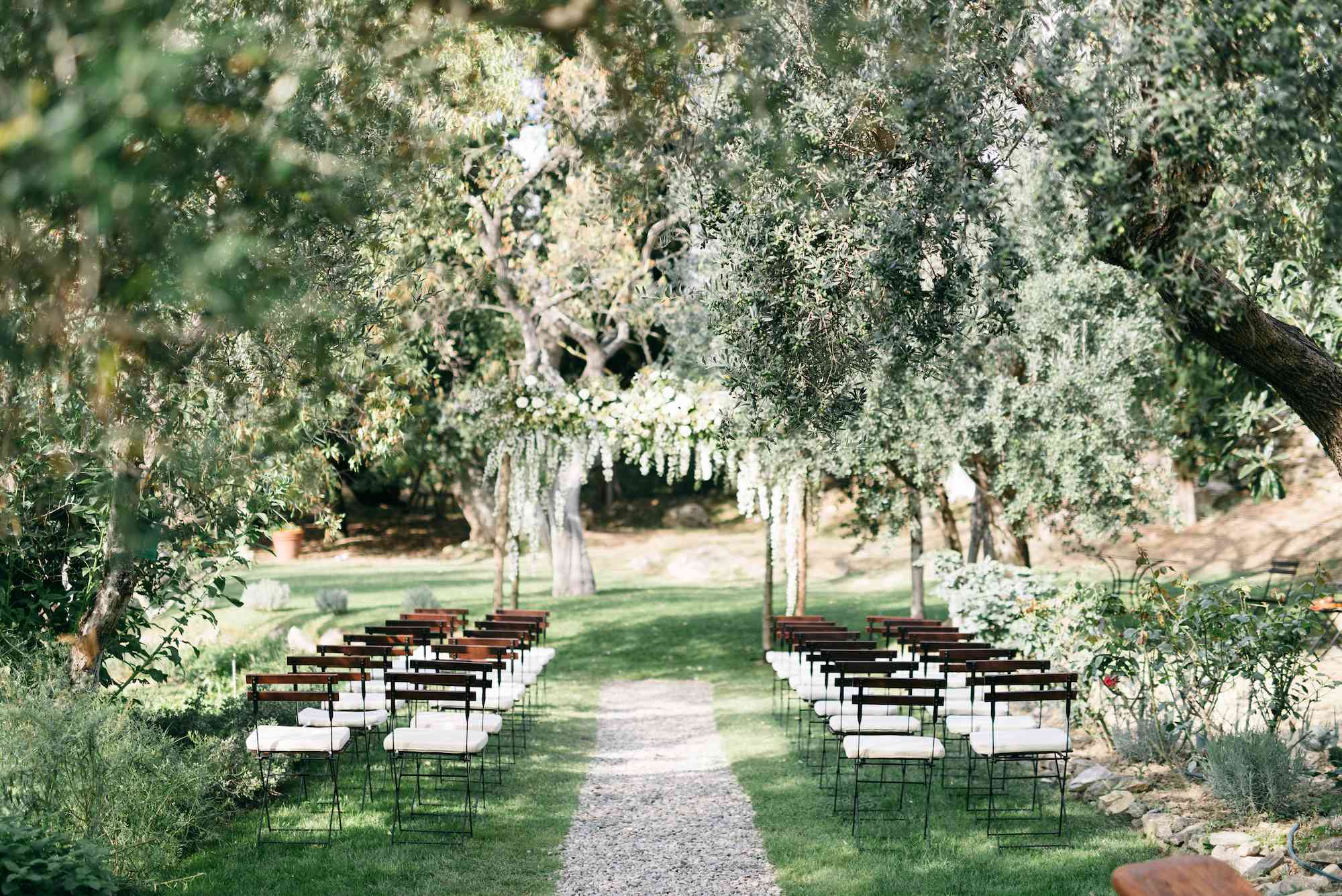 Garden wedding with a gravel aisle and greenery decor
