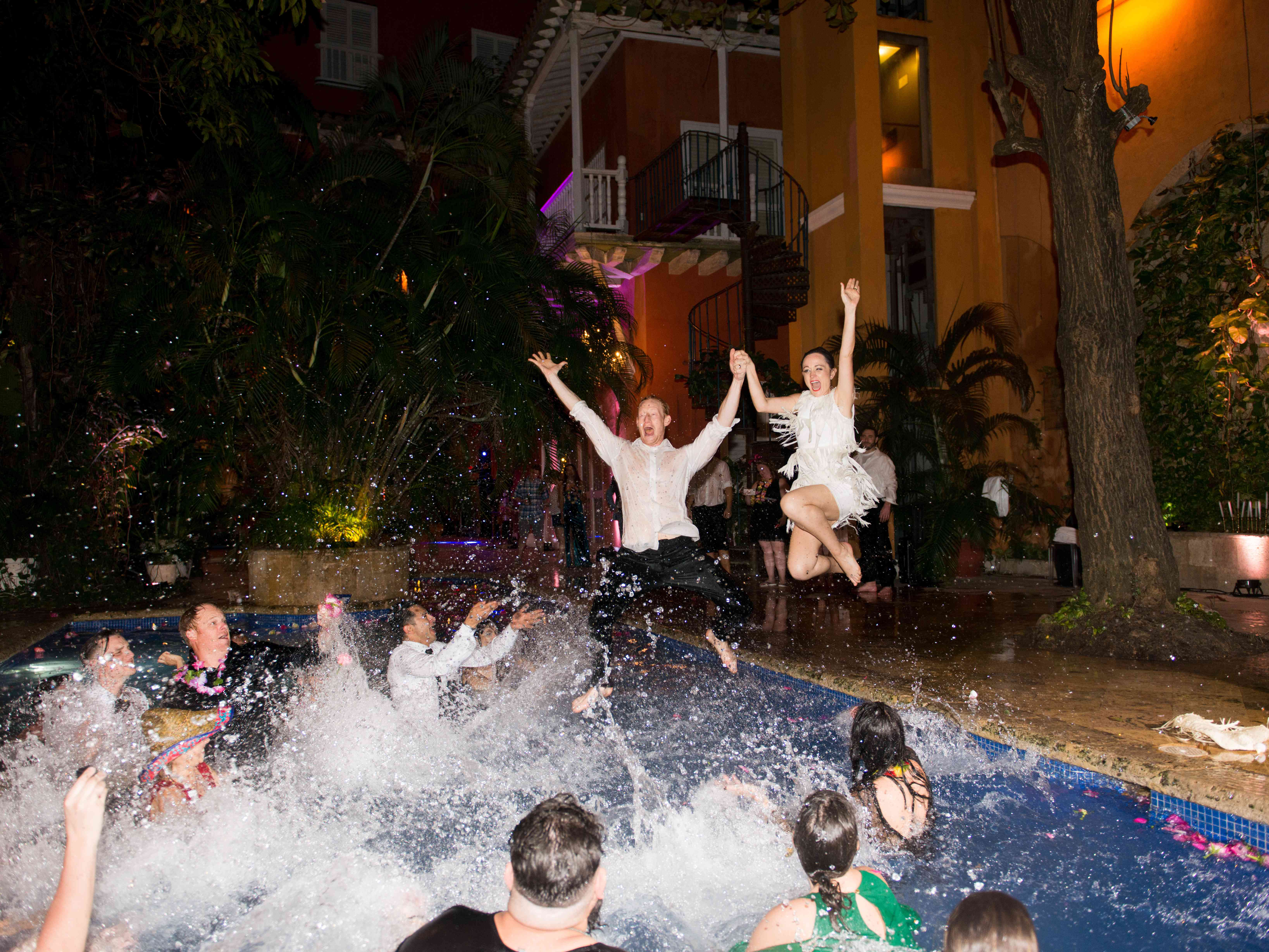 couple jumping into pool