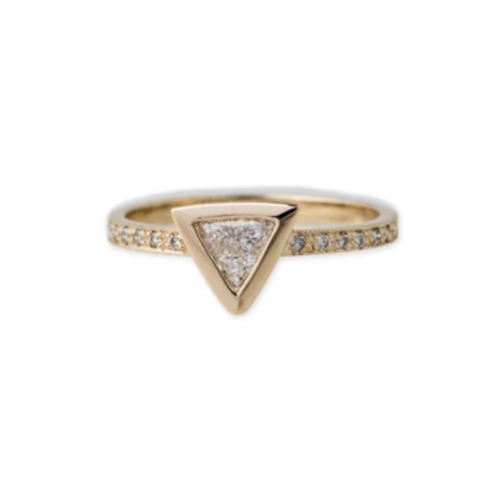 Bezel trillion diamond engagement ring with yellow gold band on a white background