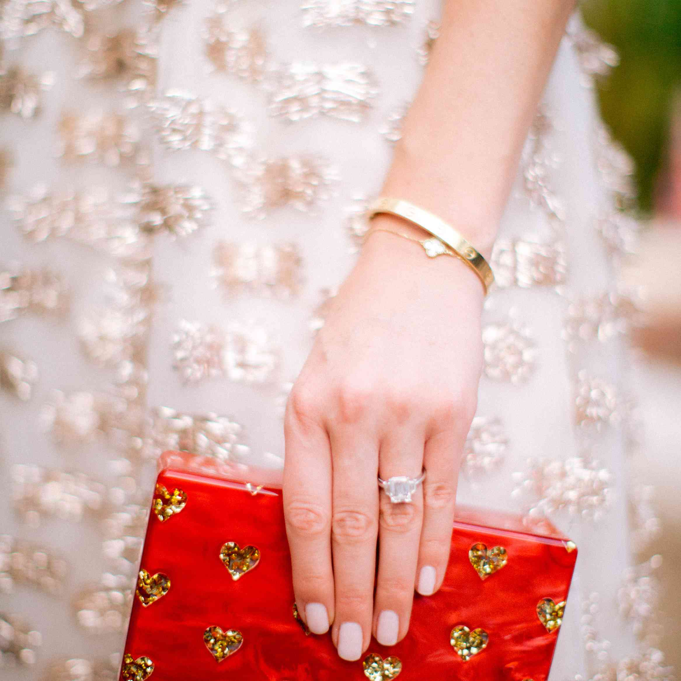 Bride carrying a red clutch with gold hearts