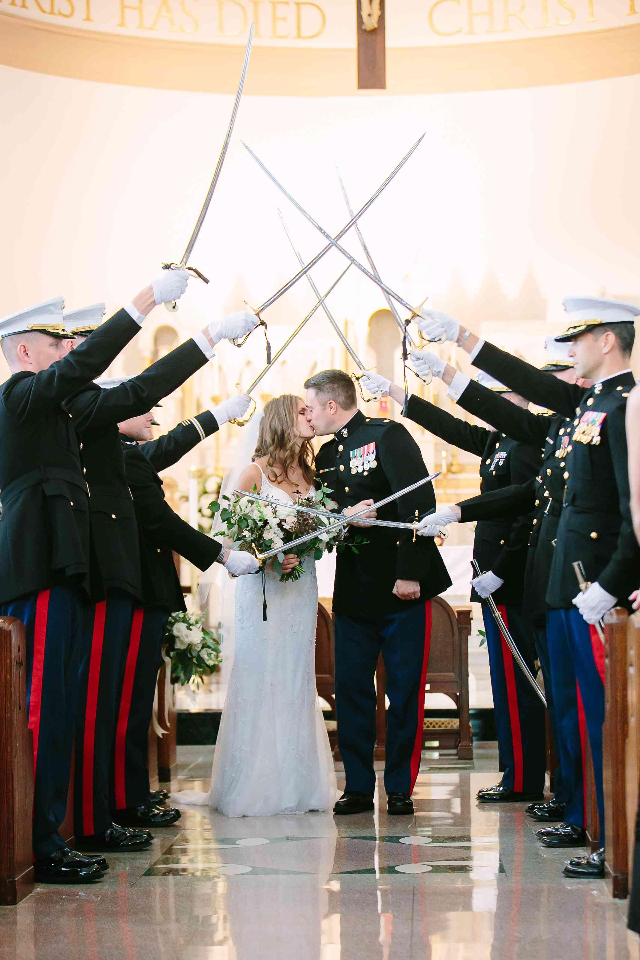 Bride and groom kissing under marine line