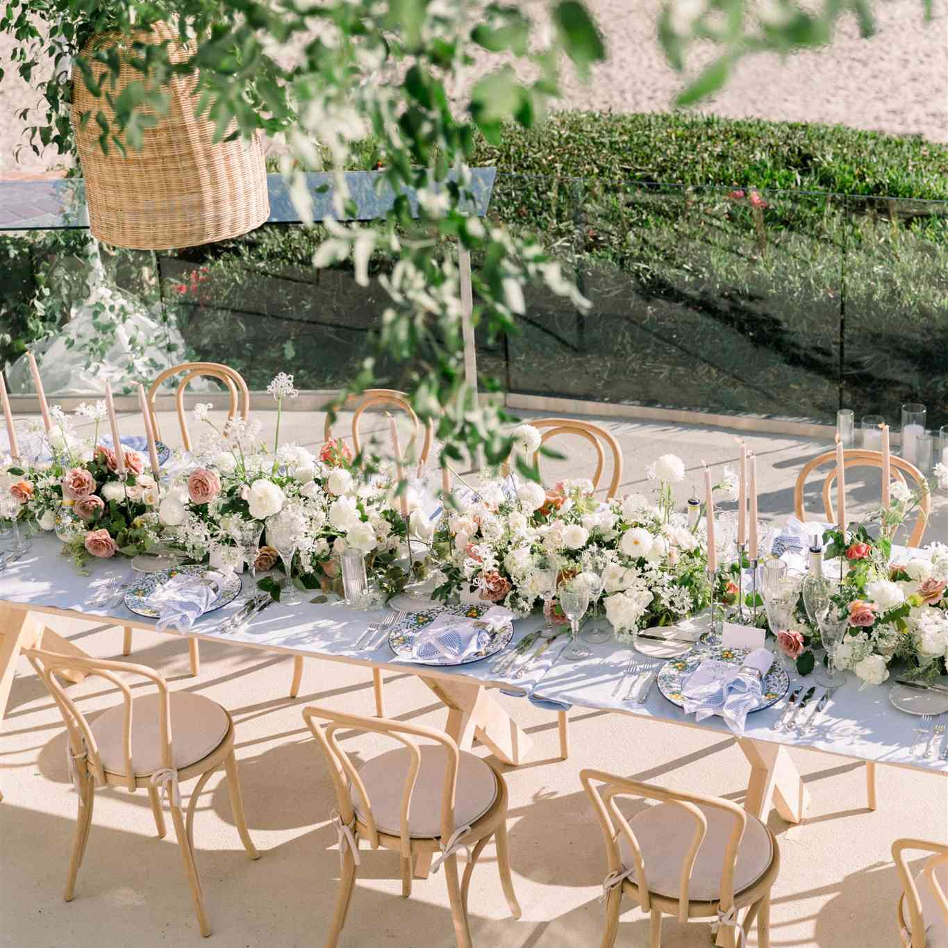 table of white and pink flowers with green garland