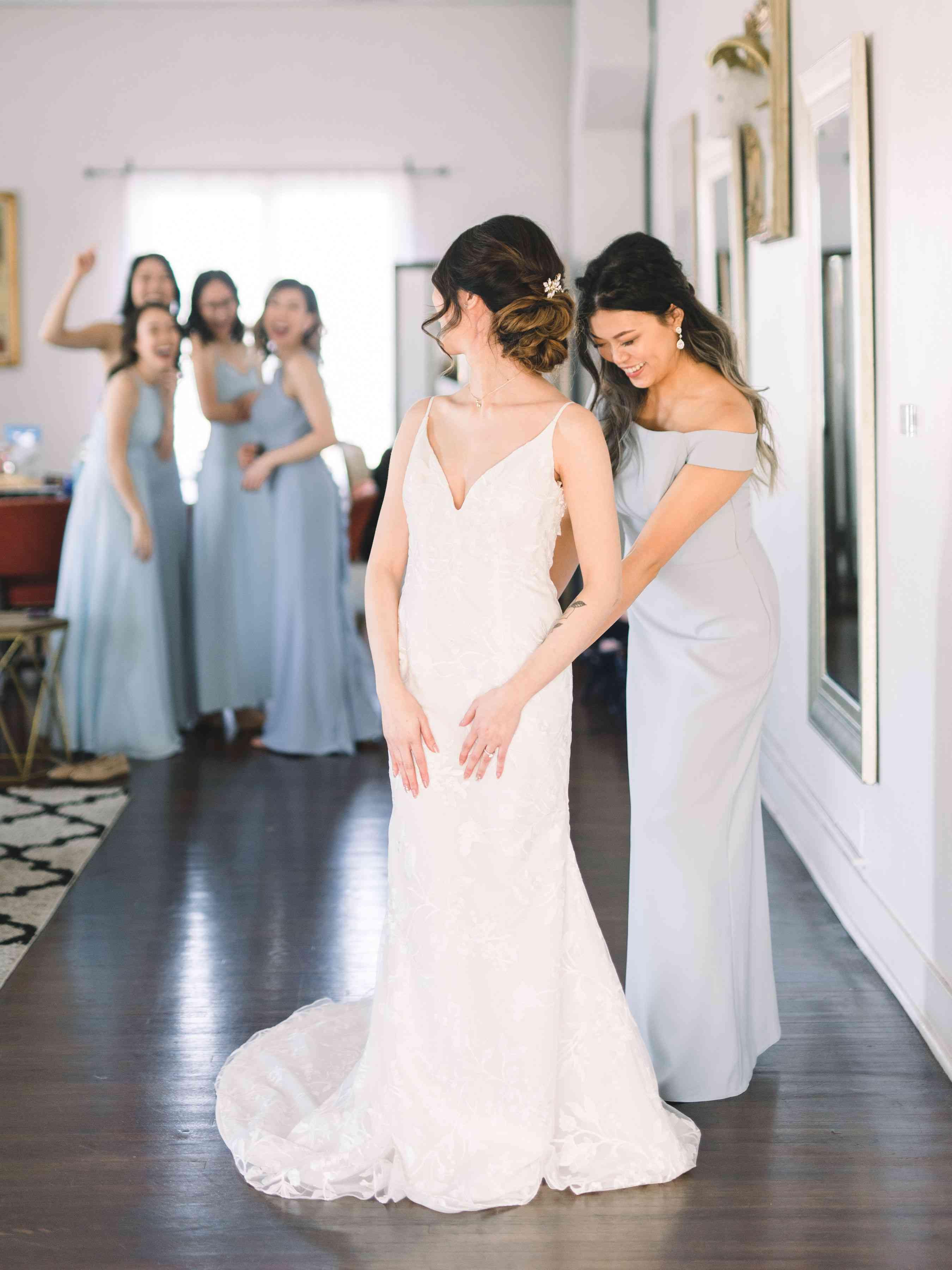 bridesmaid zipping brides dress