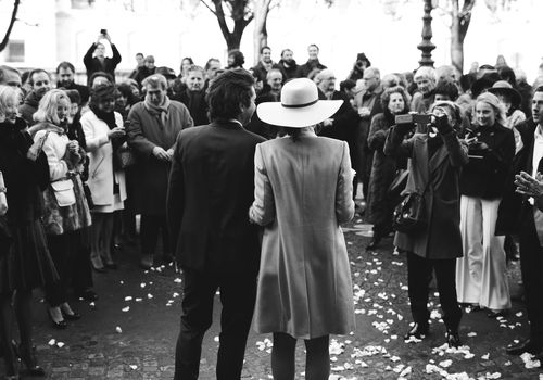 Bride and groom in front of a big crowd of their wedding guests