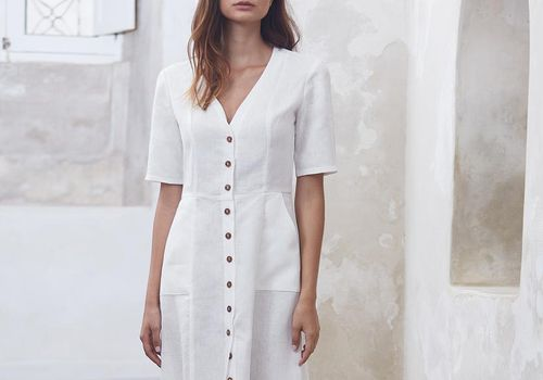 Model in button-down long white dress