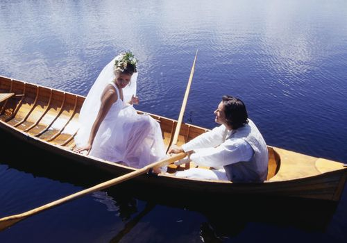 A bride and groom in a canoe.