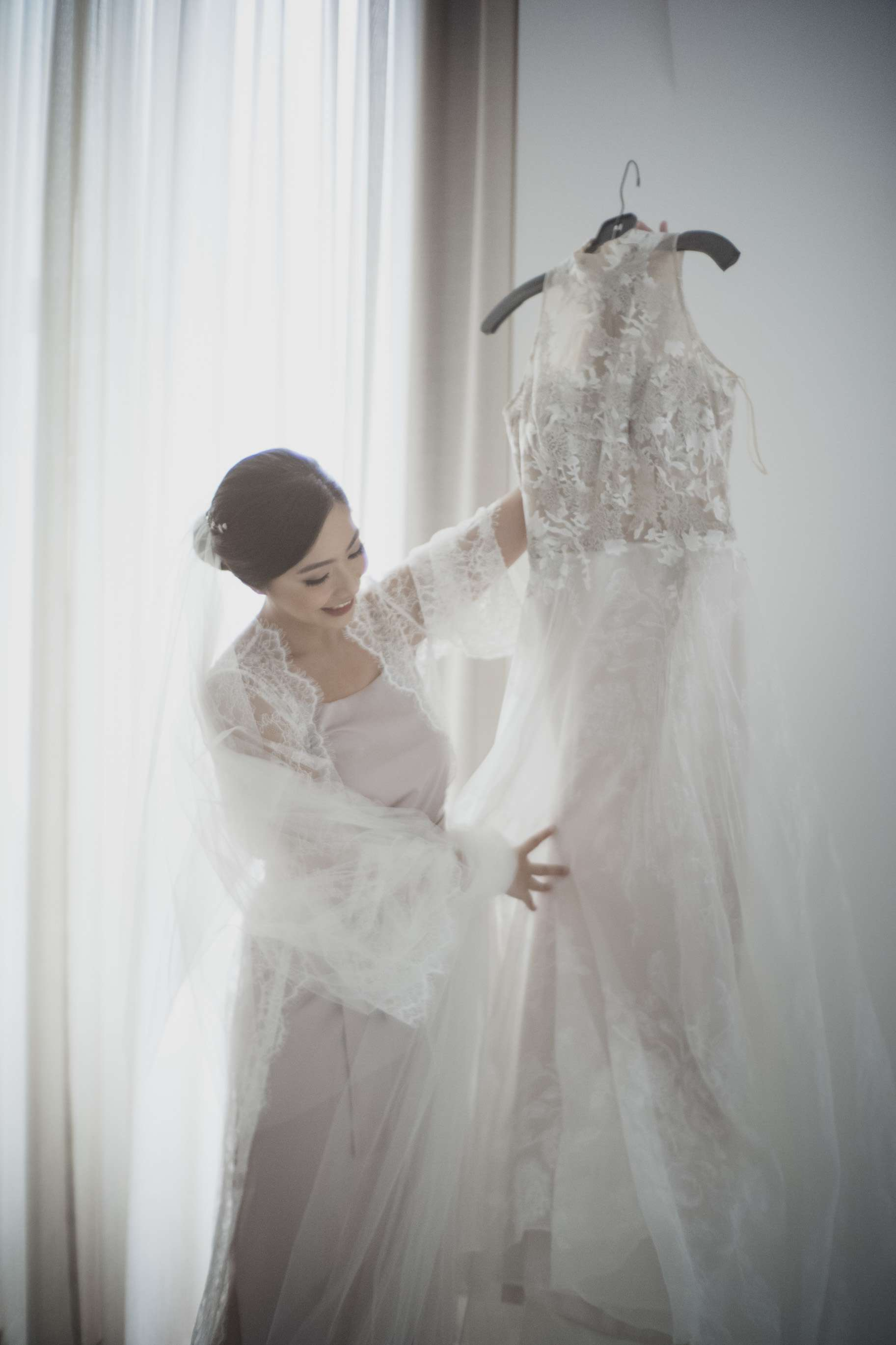 Bride holding up wedding dress