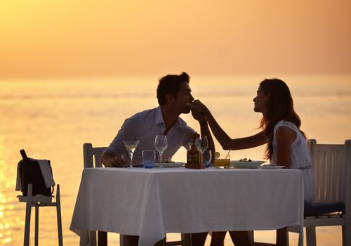 couple having a romantic sunset dinner at the beach