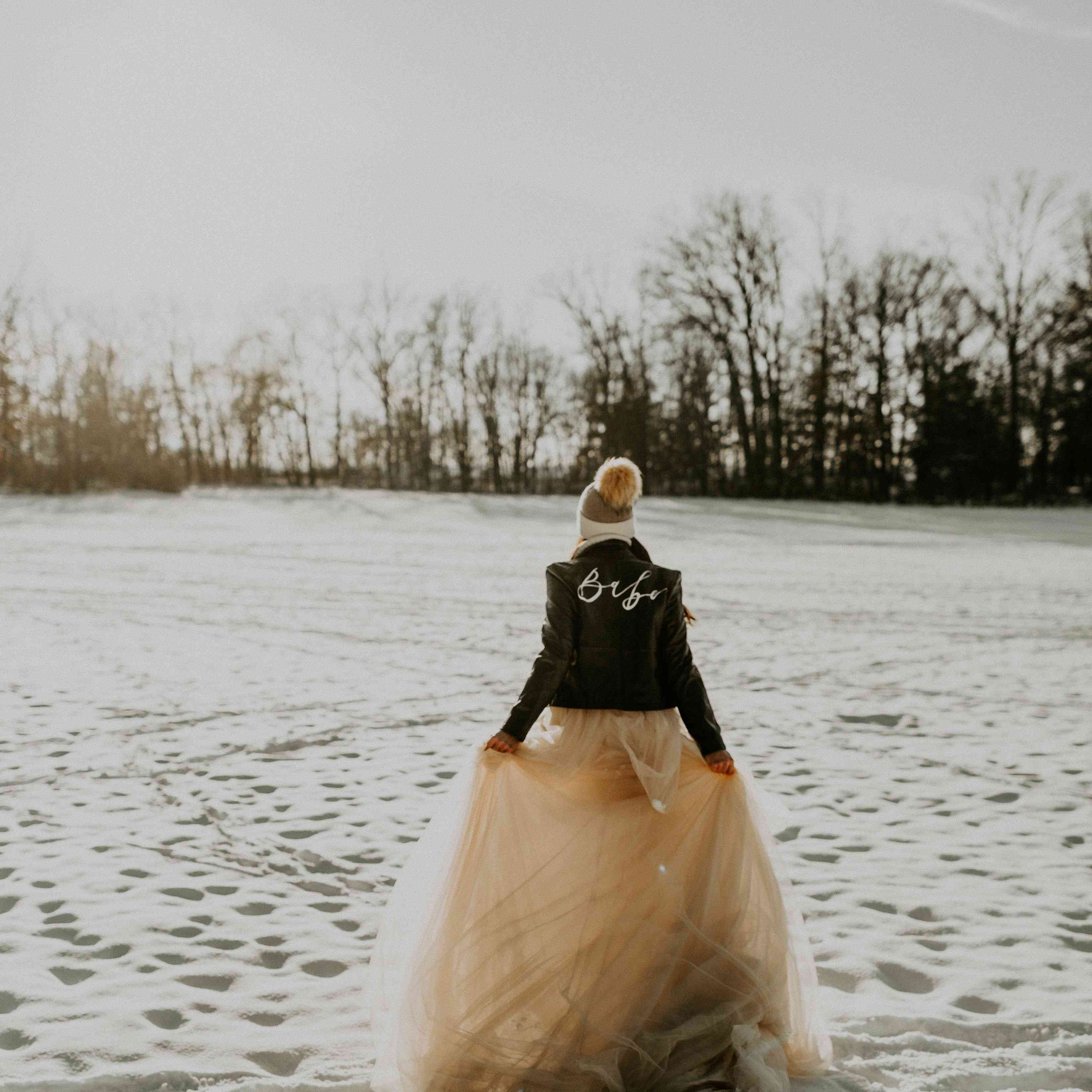 Bride walking outside in the snow wearing a leather jacket, wedding dress and hat