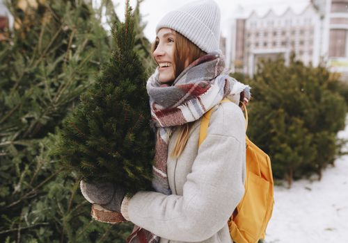 Woman holding mini pine tree