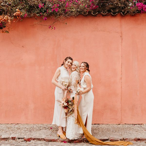 bride and bridesmaid posing in front of pink wall