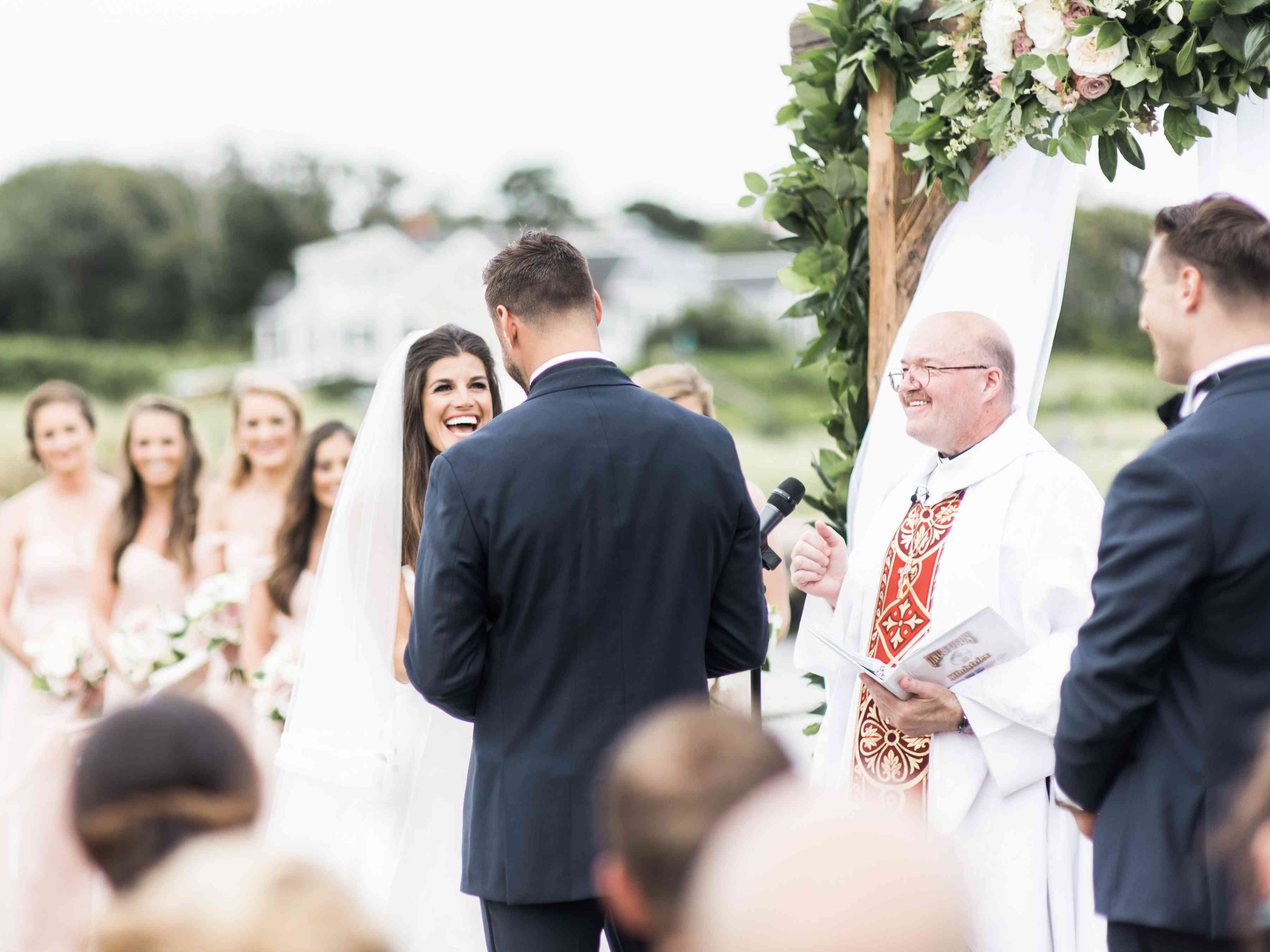 couple at altar draped in greenery and flowers