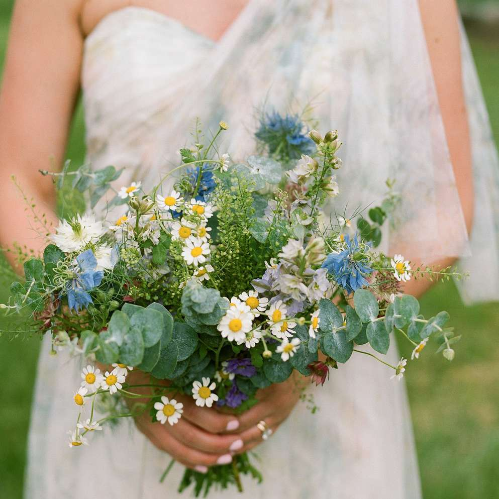 Bride holding a bouquet of pink astrantia, baby's breath, eucalyptus, lavender larkspur, baby white daisies, nigella, and blue thistle