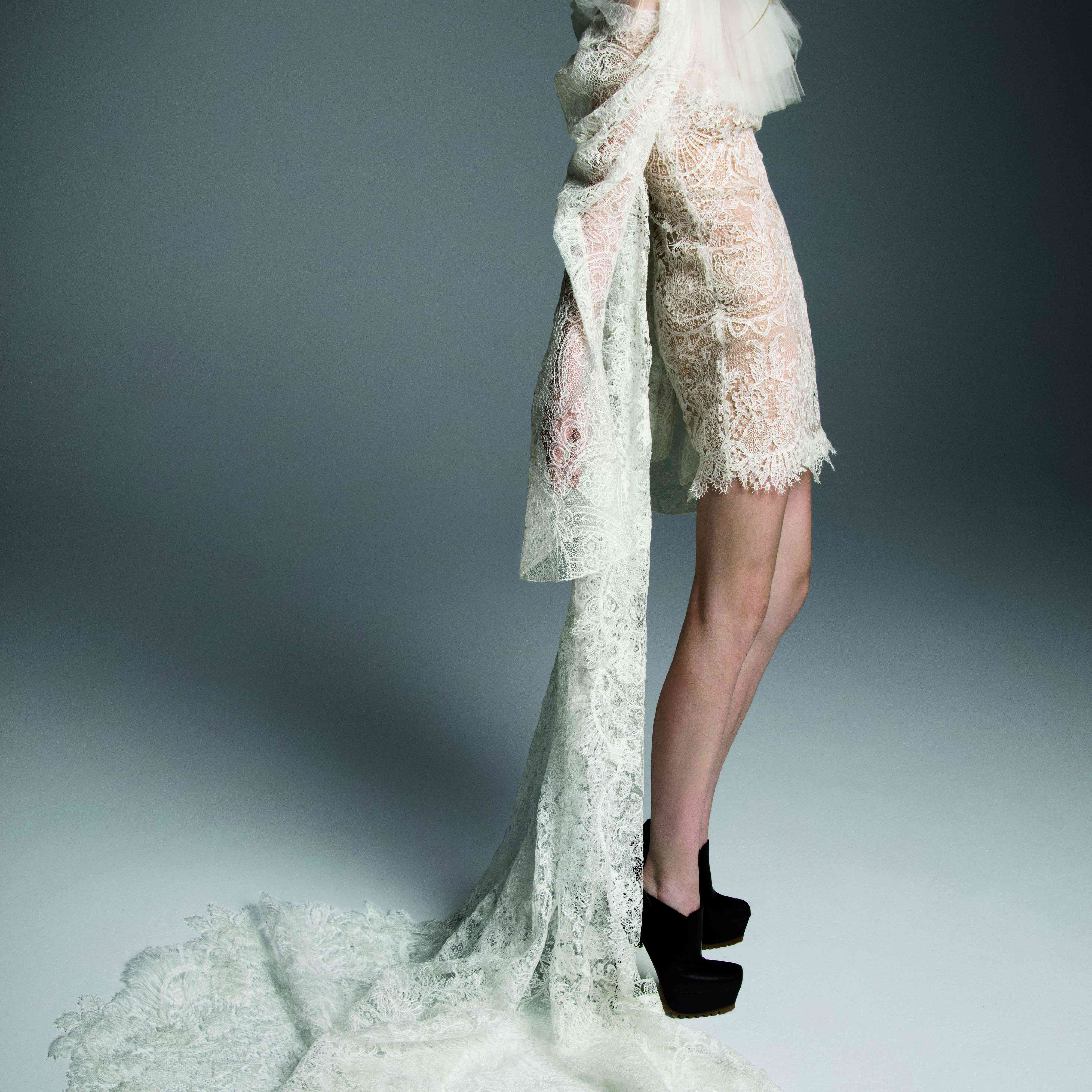 Model in lace mini dress with a watteau train and a dramatic draped sleeve