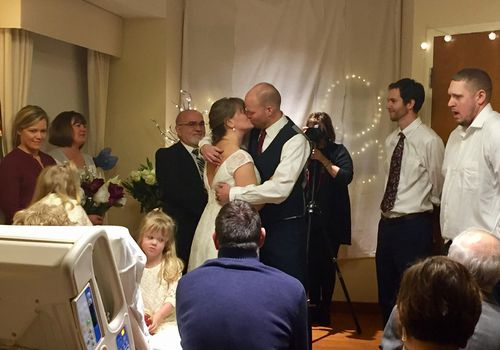 Husband and wife kissing in hospital room