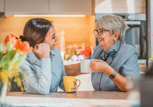 Young woman and older woman smiling with coffee mugs