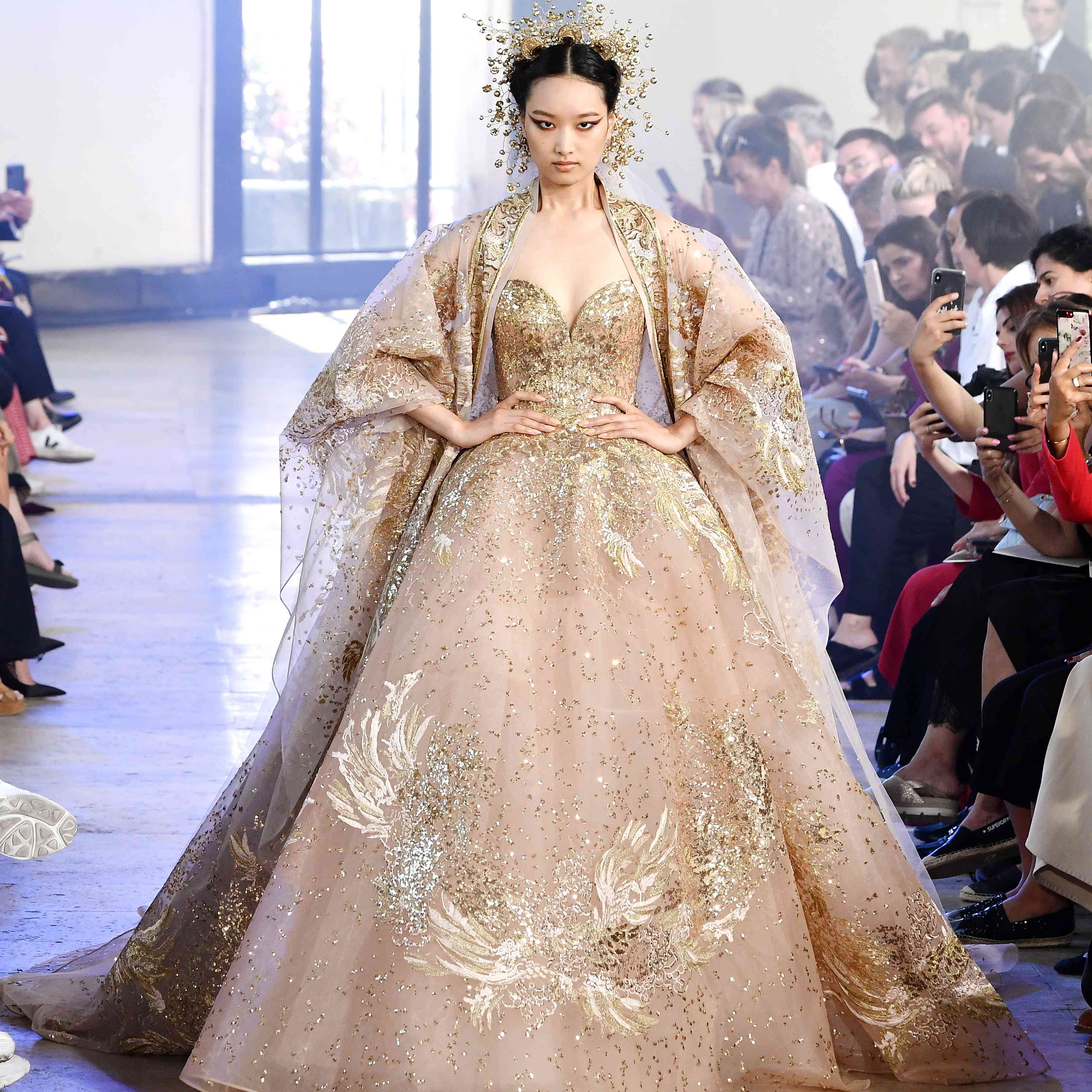 Model walking runway in gold princess wedding gown with overcoat