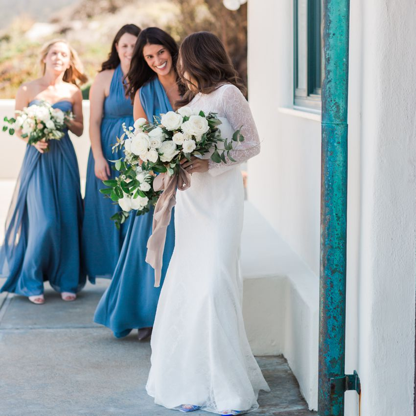 Three bridesmaids in blue walking behind a bride