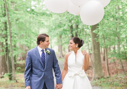 Groom and bride holding white balloons in woods