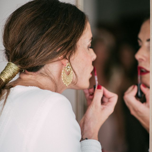Bride putting on makeup lipstick