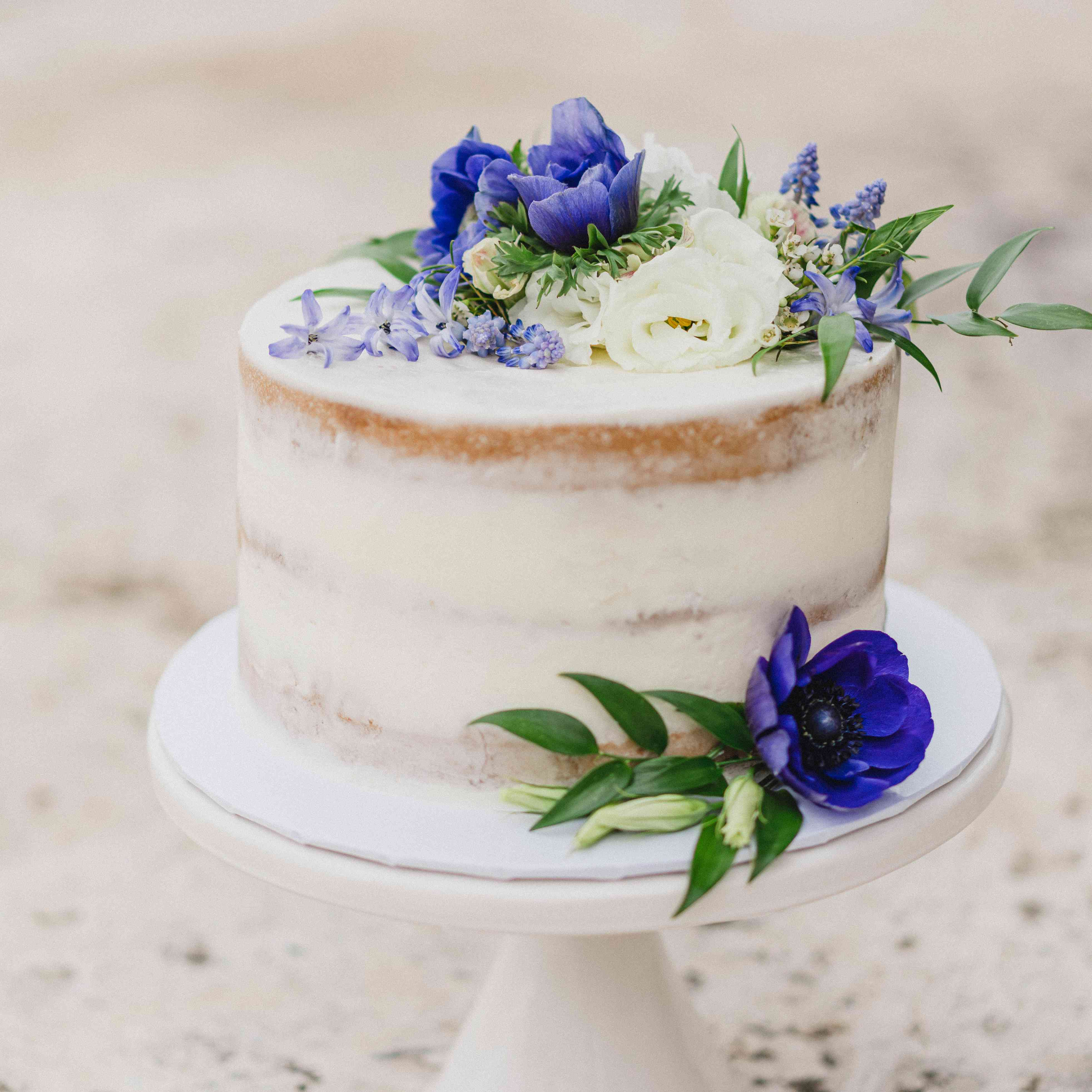 Semi-naked cake topped with violets and muscari