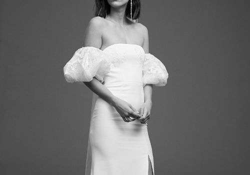 Model in off-the-shoulder gown with lace puff sleeves and skirt slit