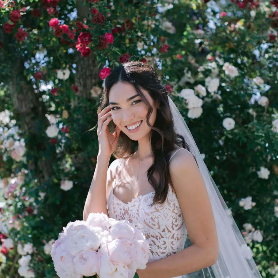 Bride smiling with peony bouquet