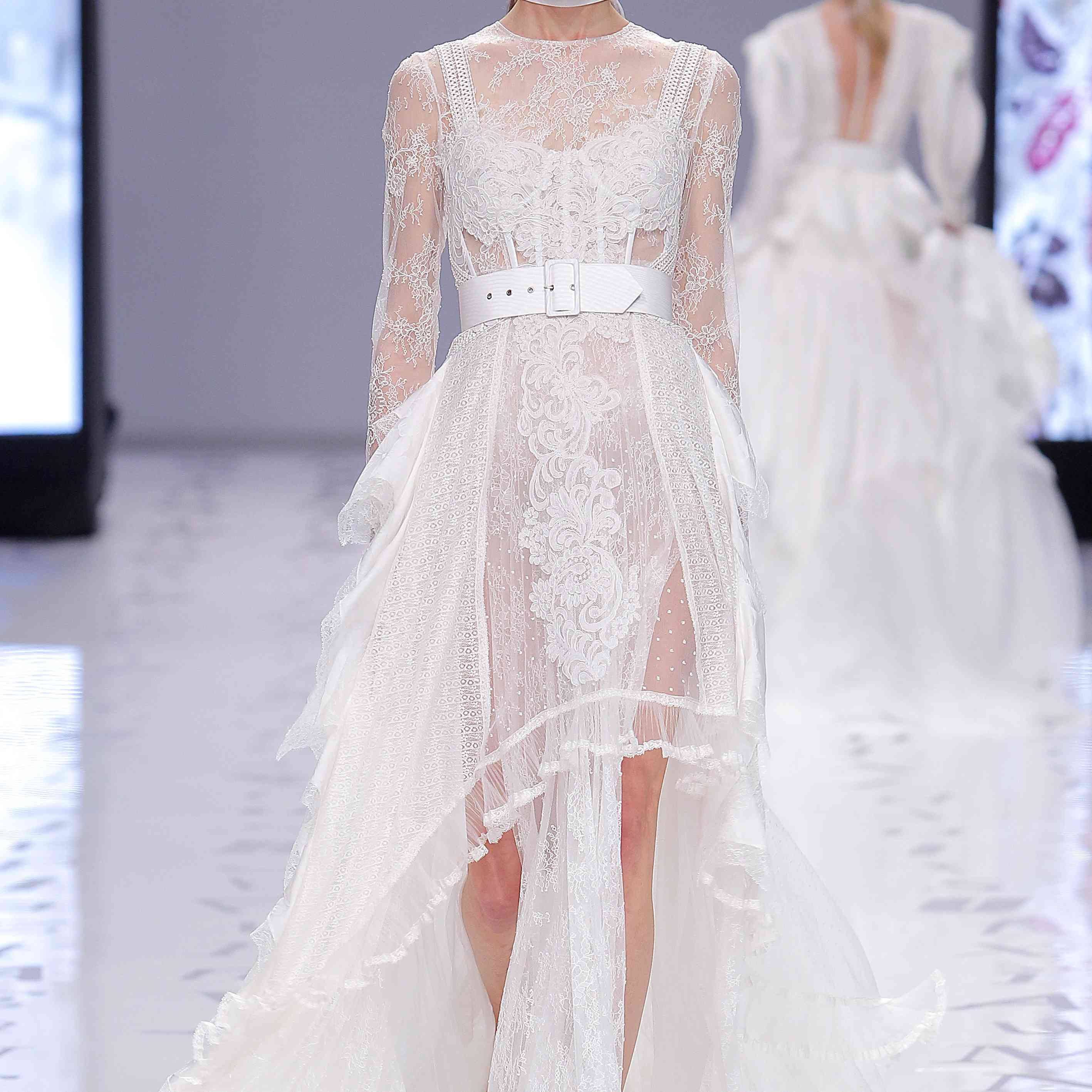Model in long-sleeve allover lace high-low gown with a white belt