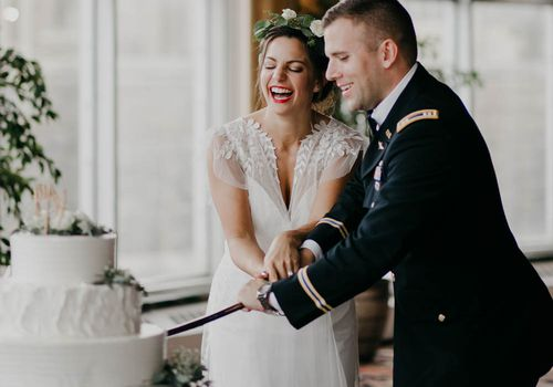 Bride and military groom cutting their cake with a military saber
