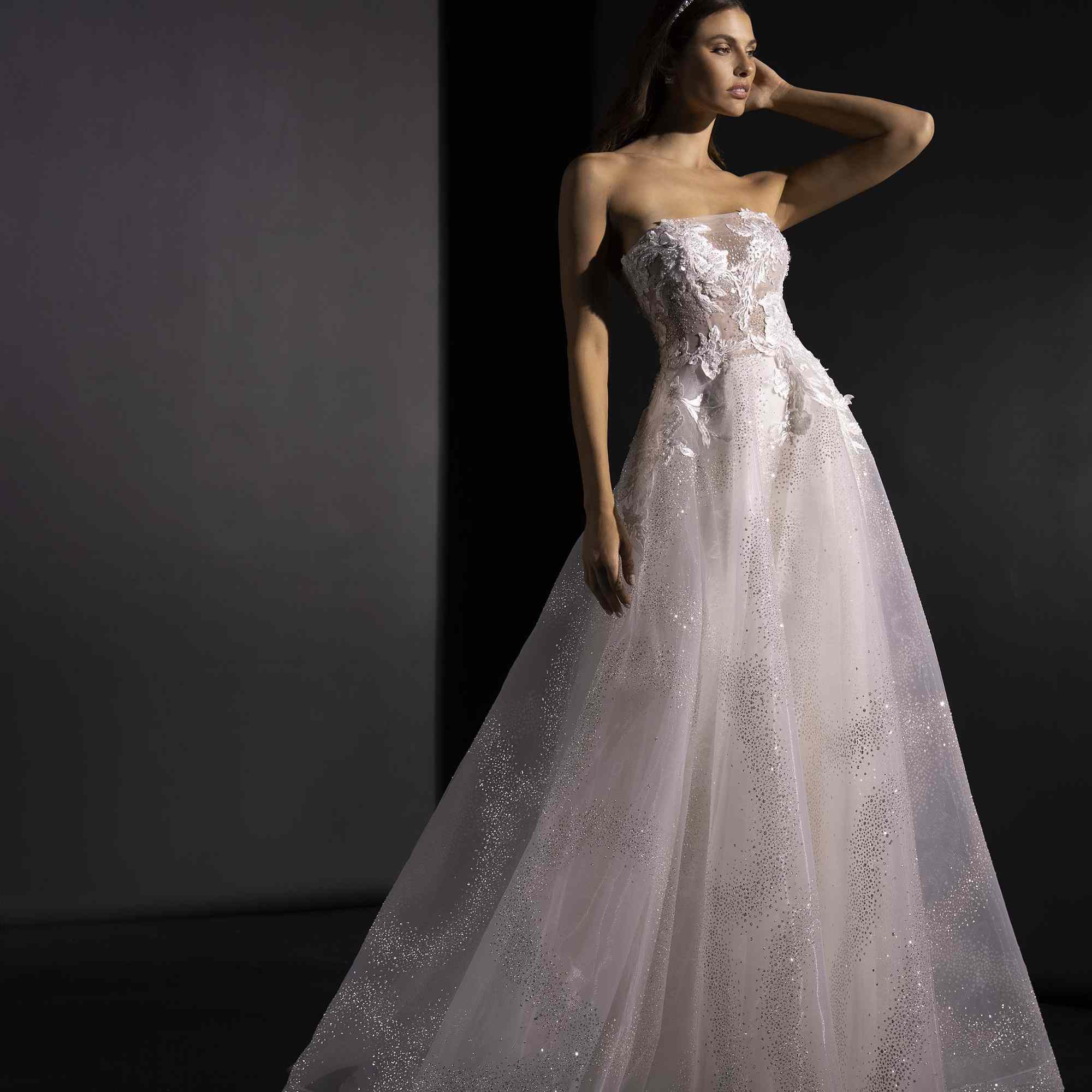 Model in strapless wispy tulle ballgown with glitter and floral appliques