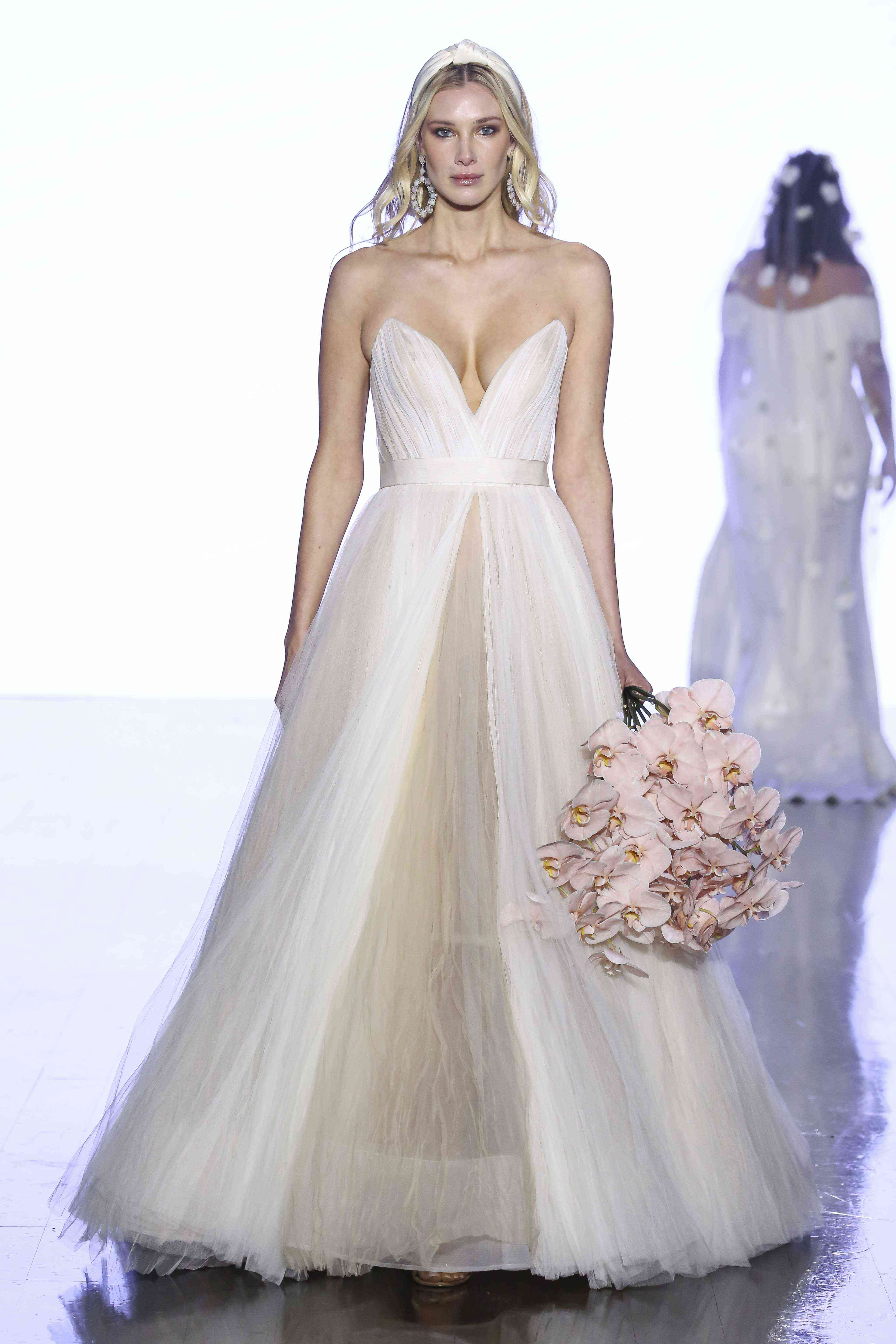 Model on runway in strapless plunging sweetheart tulle ballgown