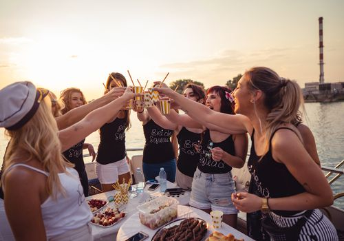 Bride squad toasting on a boat