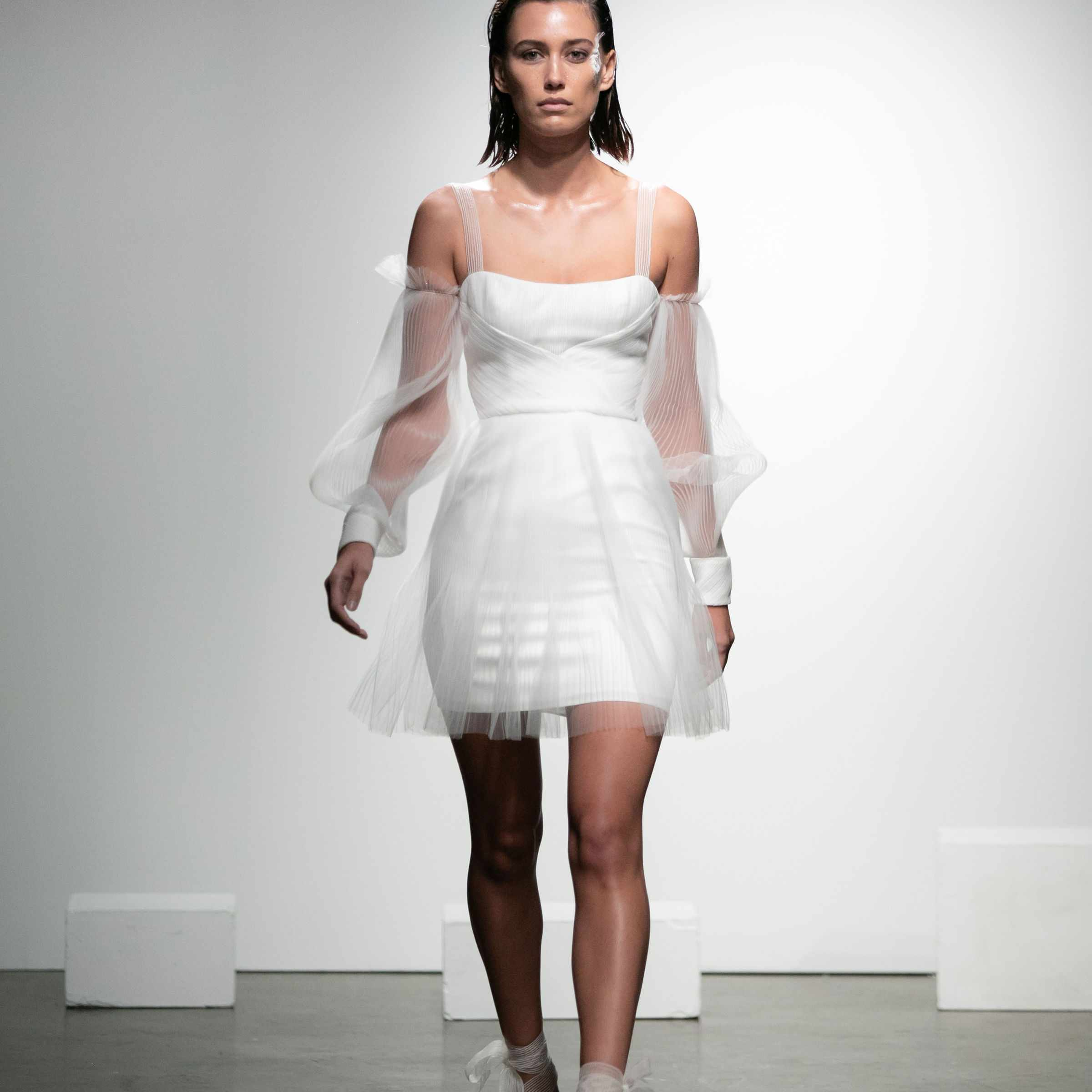 Model in pleated tulle mini dress with cold-shoulder poet sleeves