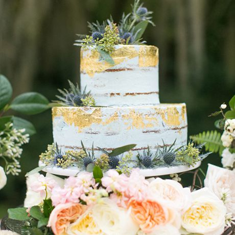 A gold and white wedding cake covered in a forest of florals and topped with fall berries