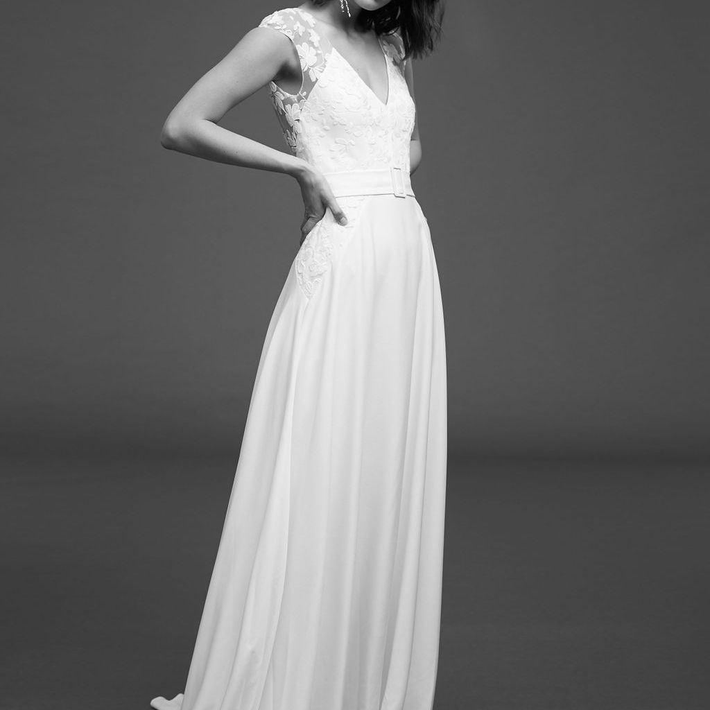 Model in A-line sleeveless crepe dress with belt