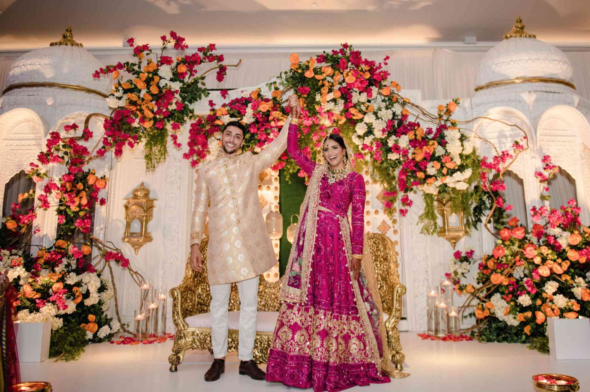 Newlyweds under floral canopy