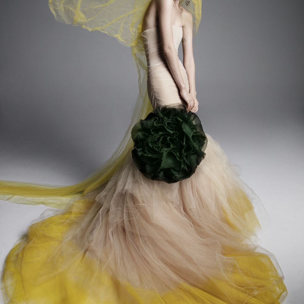 Model in strapless nude and yellow tulle mermaid gown with a dark green floral detail on the skirt