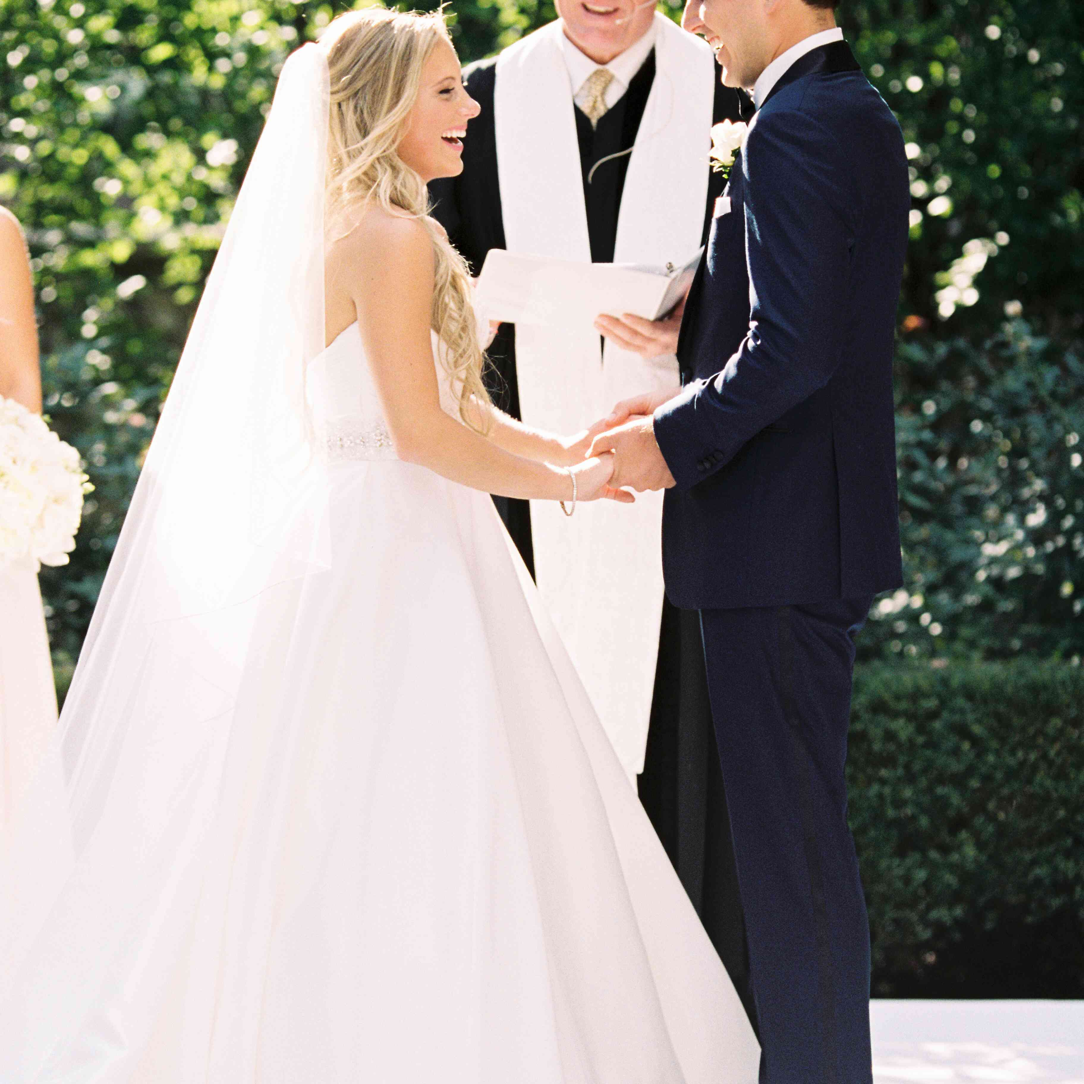 Bride and groom holding hands near ceremony