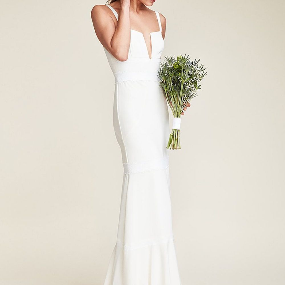 Model wearing Nicole Miller floor length bridal gown with bouquet of flowers