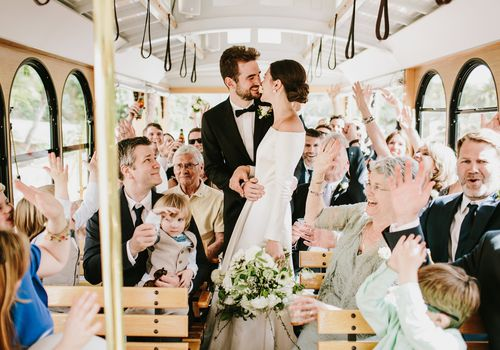 <p>bride and groom on trolley with guests</p>