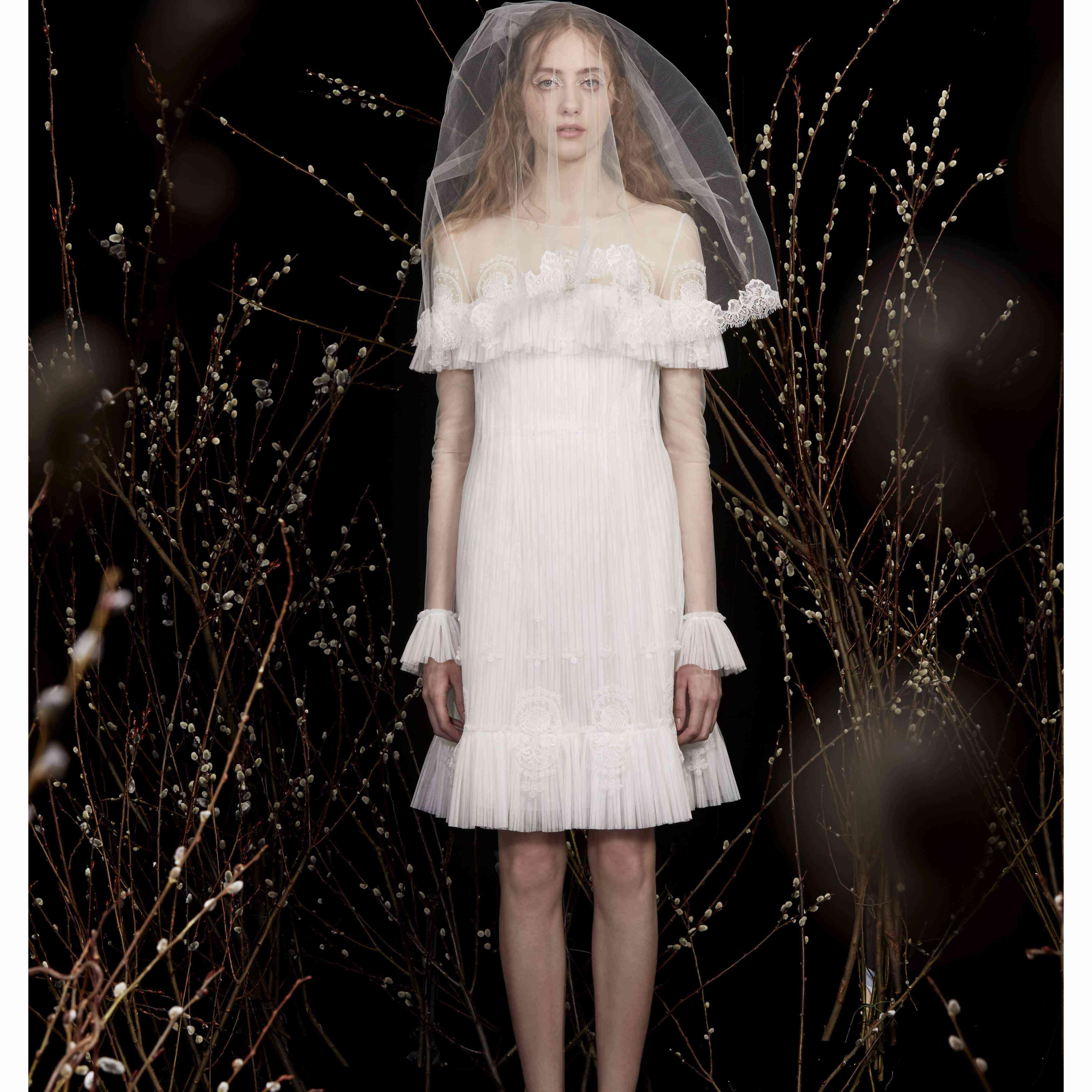 Model in long sleeve pleated mini wedding dress